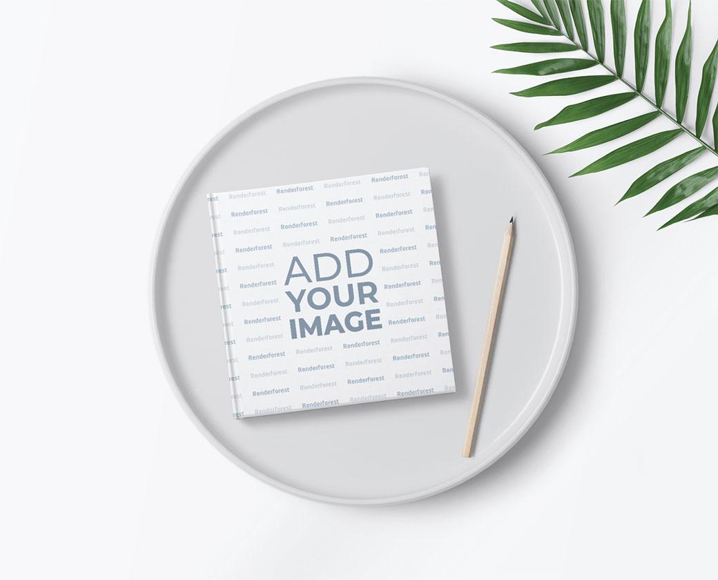 Carnet de croquis carré et un crayon avec une plante