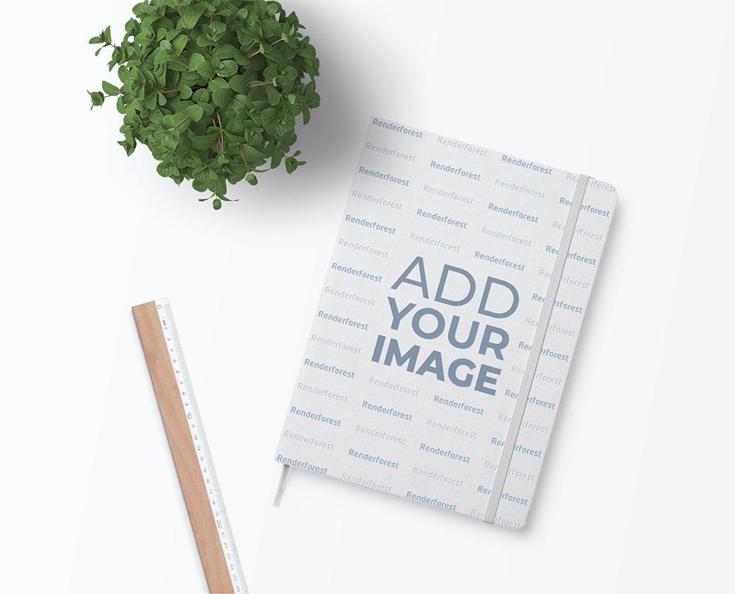 Elastic Band Sketchbook, a Ruler, and a Plant