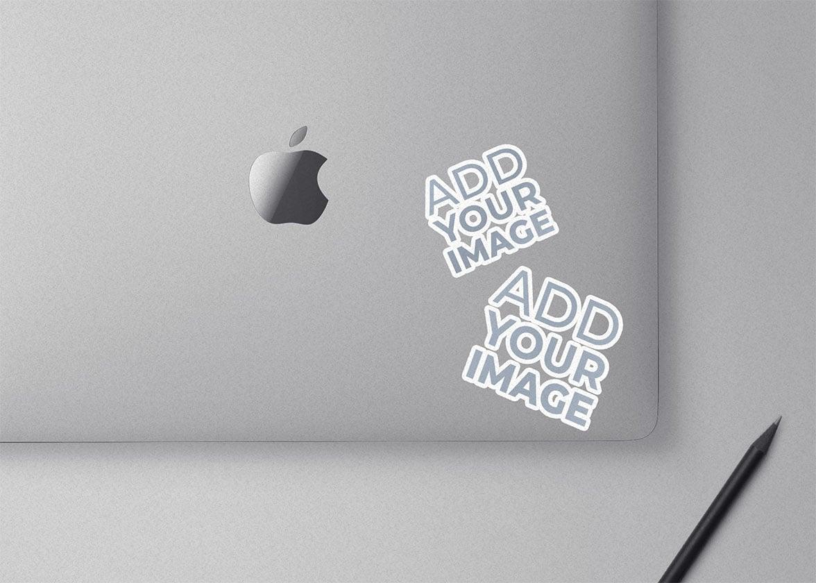 Dois Adesivos em um Macbook com um Lápis