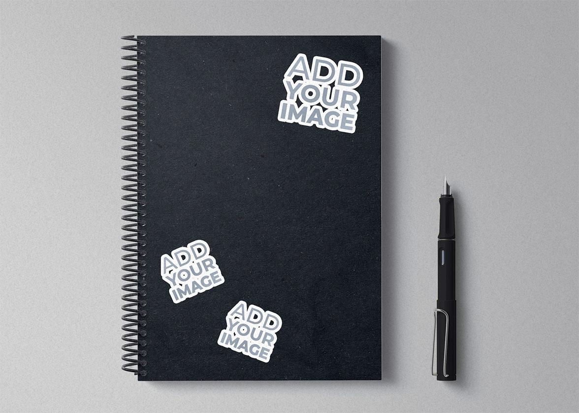 Três Adesivos em um Caderno Espiral