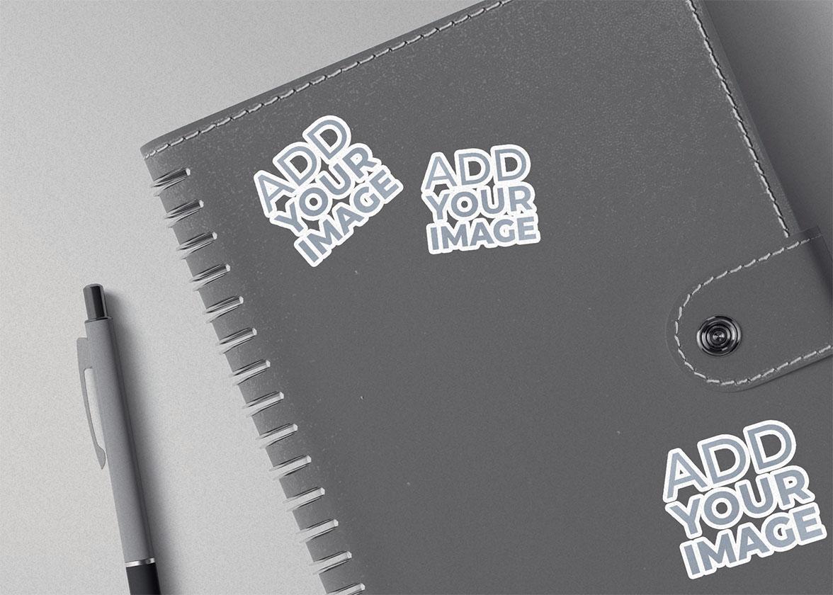 Três Adesivos em um Caderno de Desenho com Botão