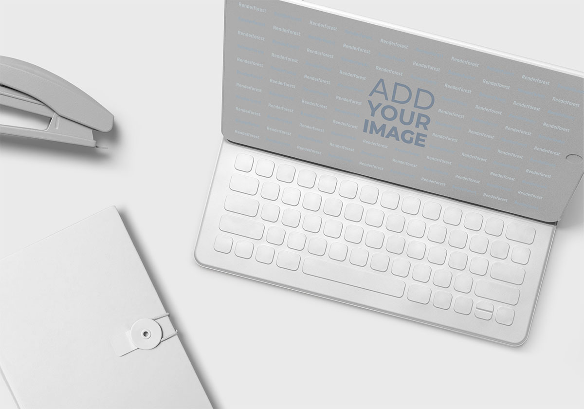 MacBook, um Caderno com Botão e um Grampeador