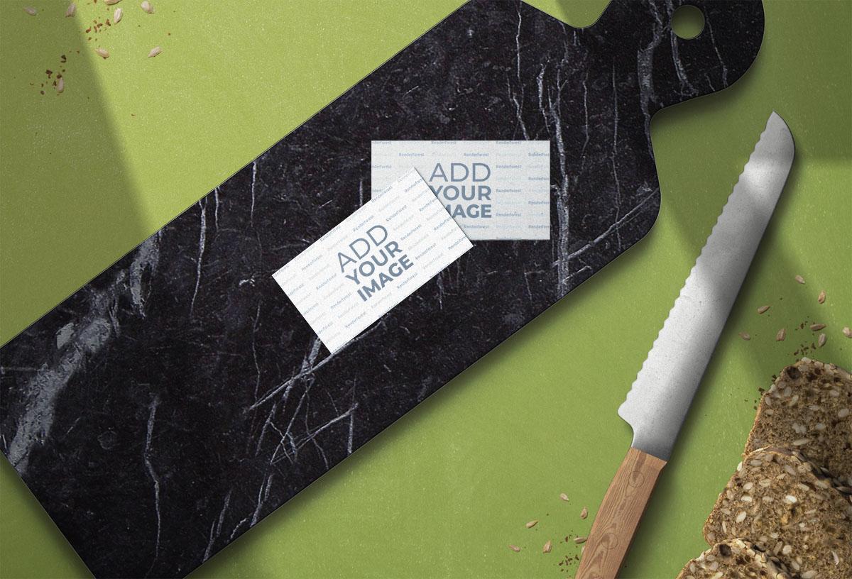 Dos tarjetas de visita sobre una tabla de cocina de mármol