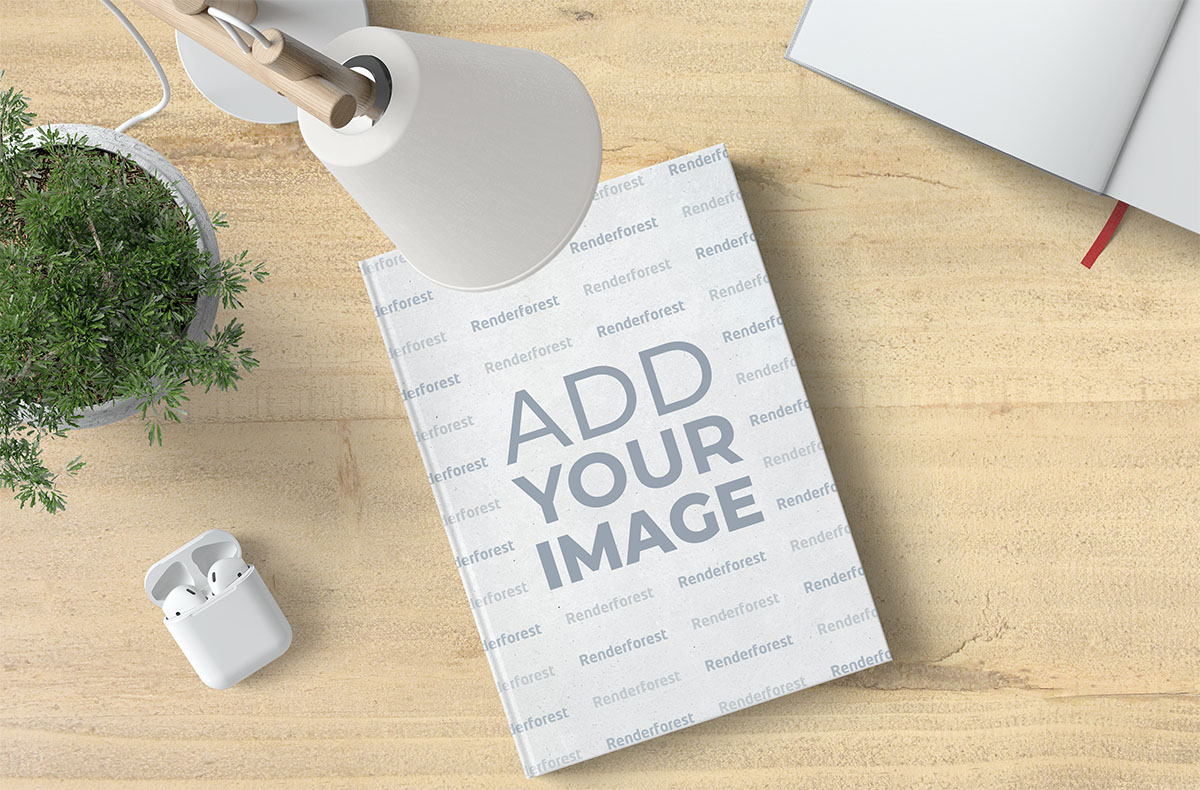 Libro, AirPods y una lámpara de escritorio
