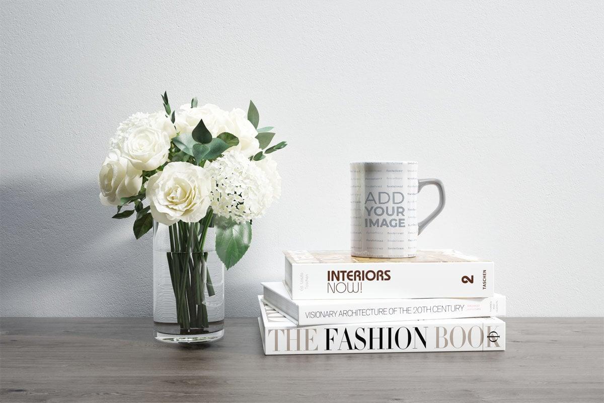 Flores y una taza cuadrada sobre libros
