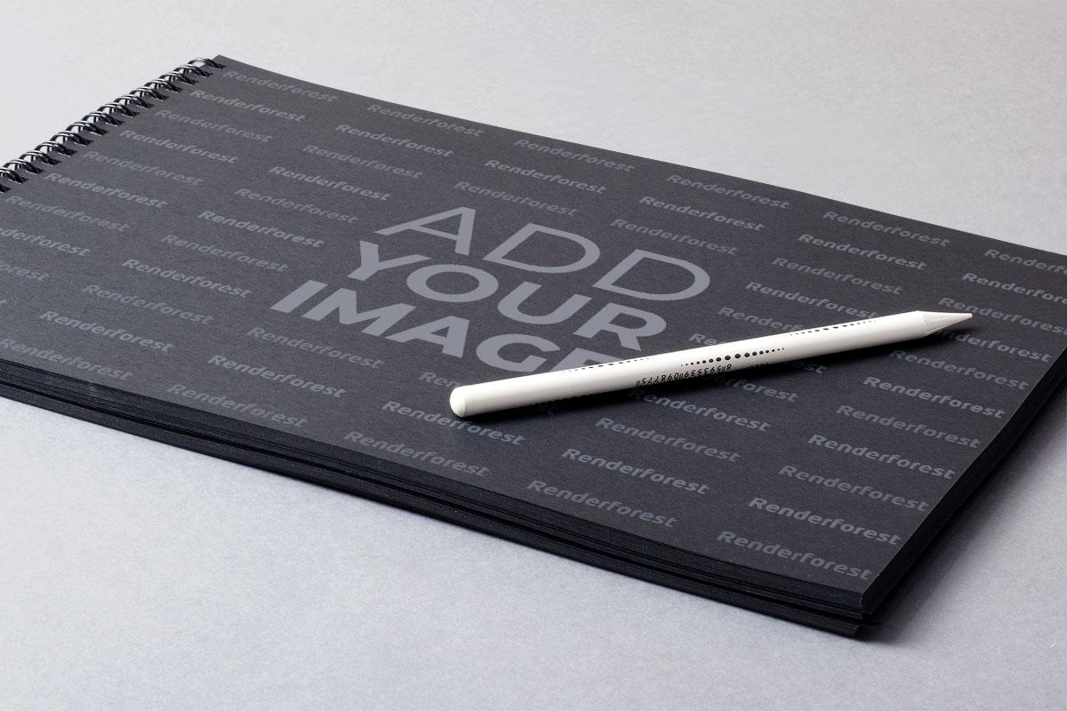 Lápiz blanco sobre un cuaderno de bocetos negro con espiral