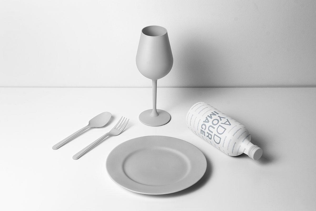 Teller und Besteck mit einer Flasche und einem Glas