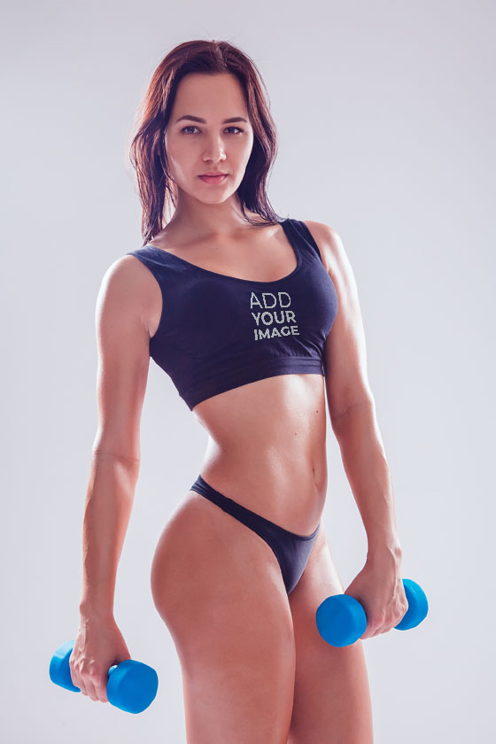 Sport Girl in a Short Tank Top with Dumbbells