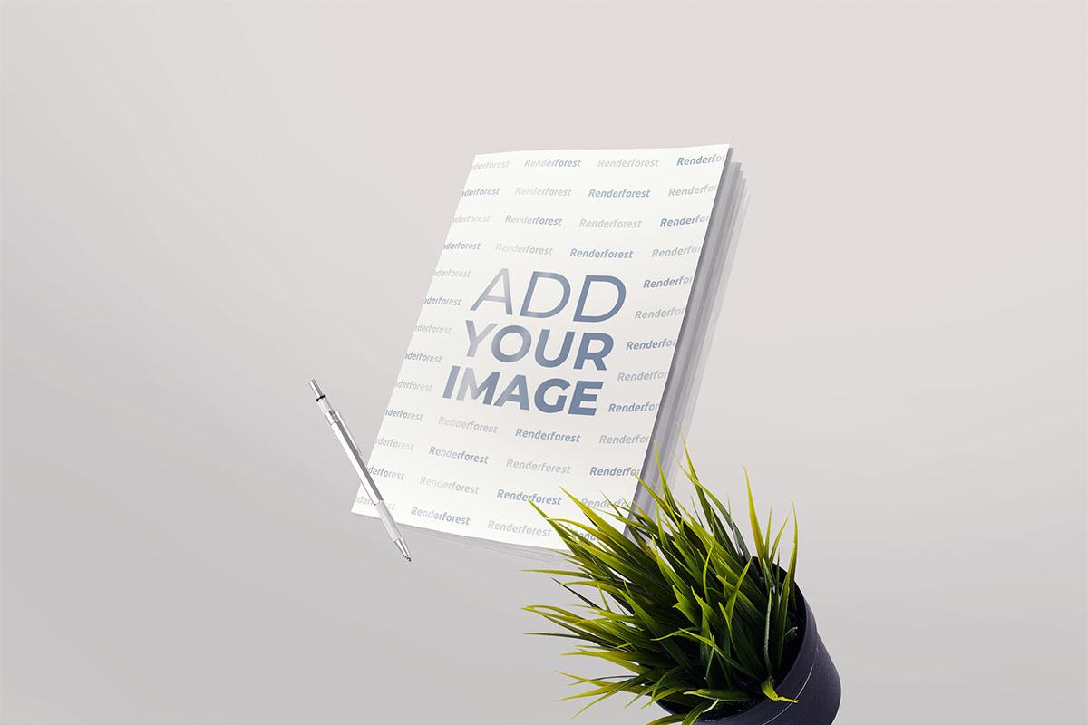 Softcover-Notizbuch, ein Stift und ein Pflanztopf in der Luft